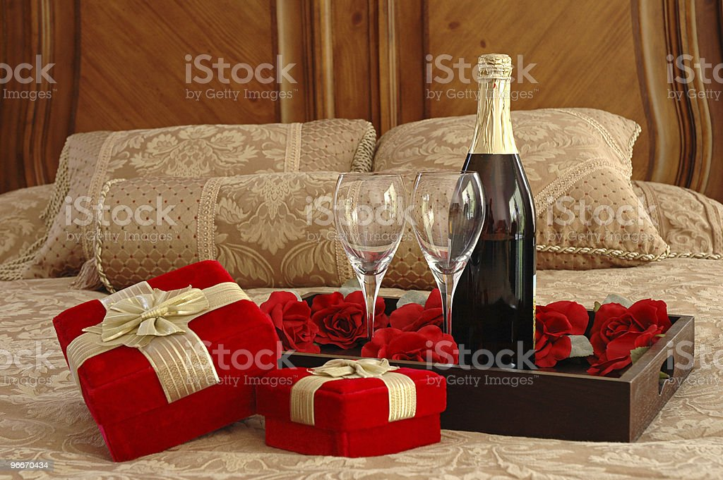 Romantic setting of wine and presents on a bed stock photo