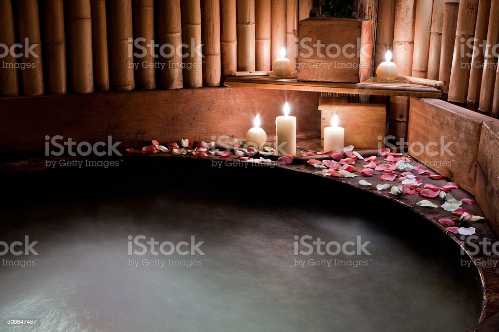 Romantic spa - jacuzzi tub with rose petals stock photo