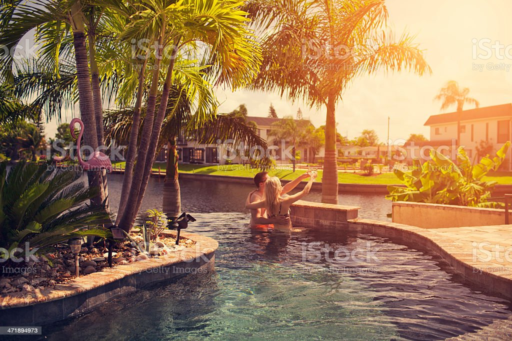 Romantic sunset couple relaxing at tropical pool stock photo