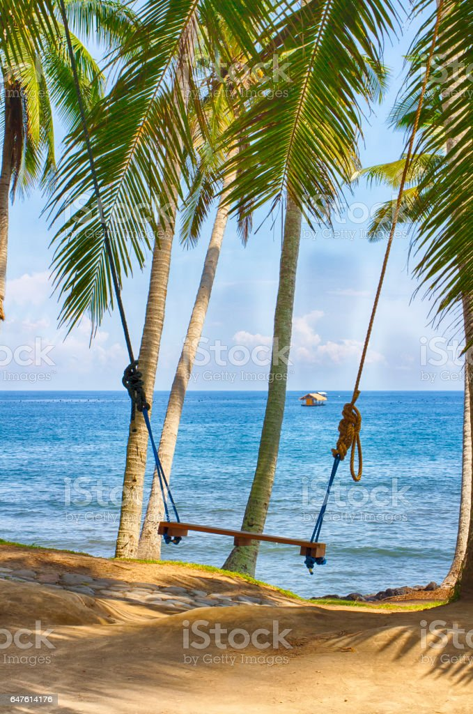 Romantic swing on the shore of the Indian Ocean. Wedding attribute. stock photo