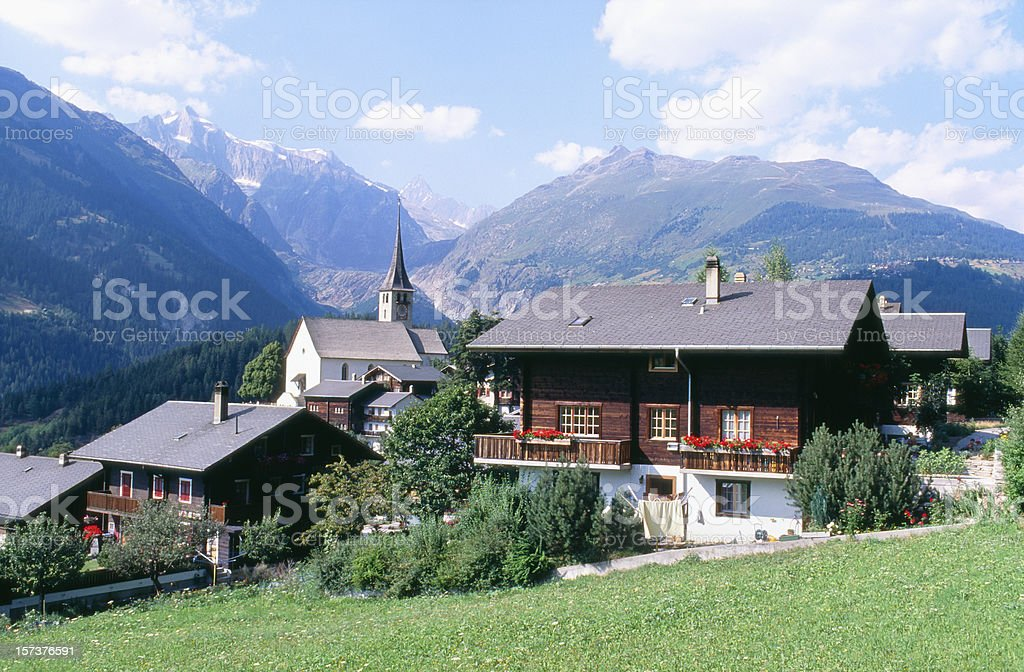 Romantic Swiss village with houses, church and mountains royalty-free stock photo