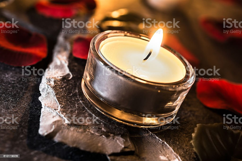 Romantic Tealight On Slate With Rose Petals And Leafs stock photo