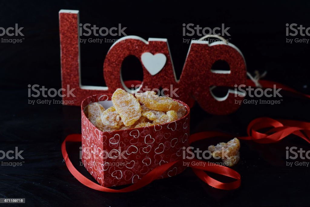 Romantic theme. Box with candied orange slices, Love sign on black abstract background. St. Valentine's day stock photo