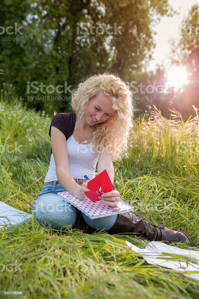 Romantic woman writing a love letter in the park. stock photo