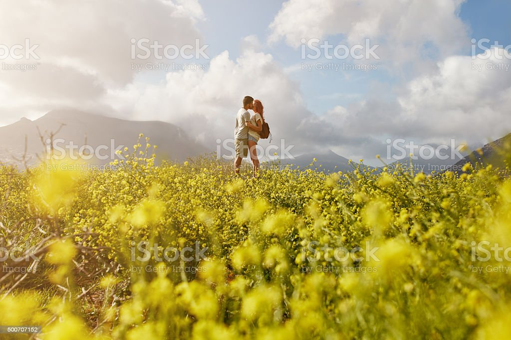 Romantic young couple embracing and kissing on summer day stock photo