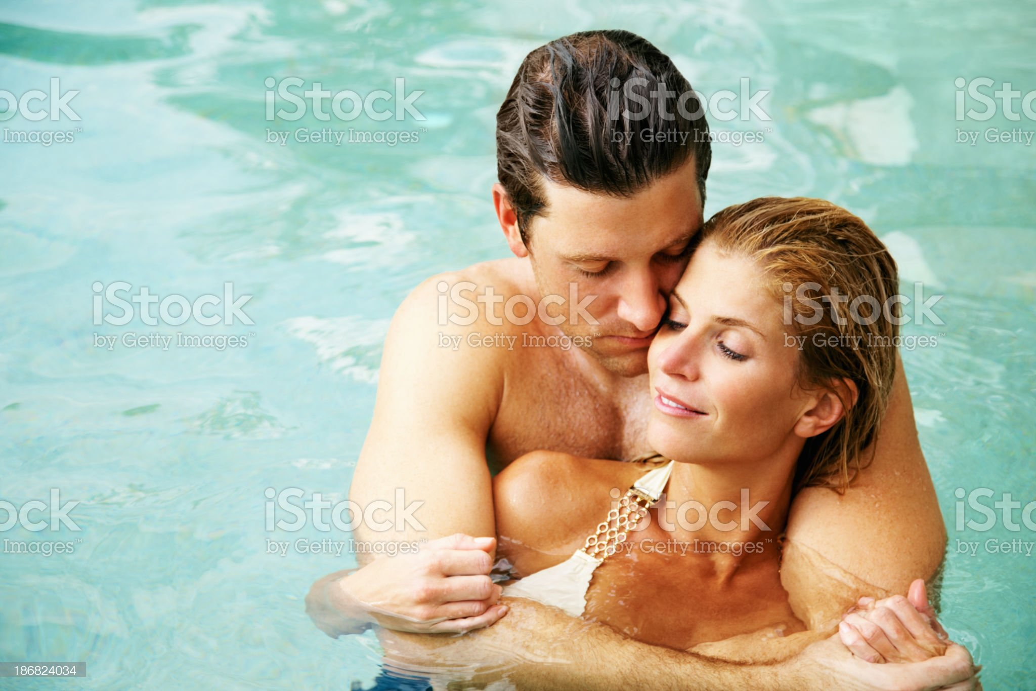 Romantic young couple embracing in swimming pool royalty-free stock photo