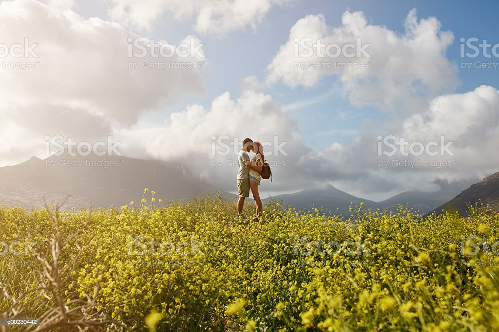 Romantic young couple embracing on hill top stock photo