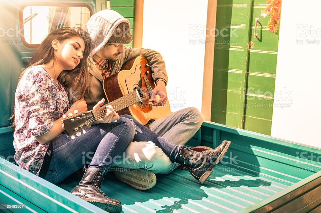 Romantic young Couple of lovers playing Guitar stock photo