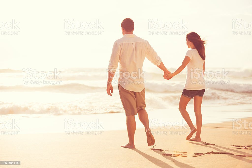 Romantic Young Couple on the Beach at Sunset stock photo