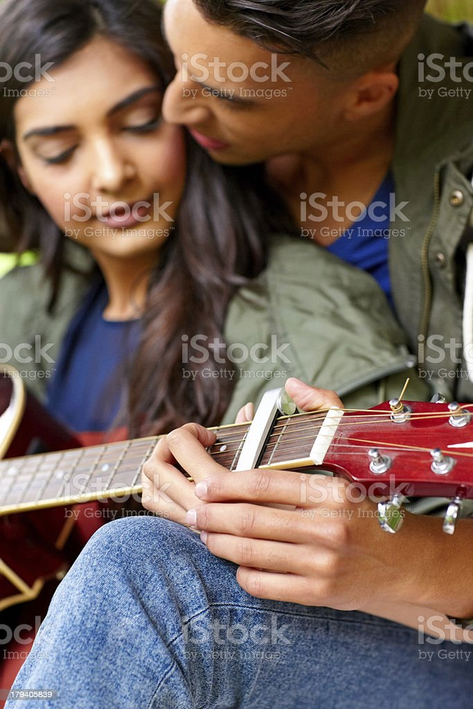 Romantic young couple playing guitar together royalty-free stock photo