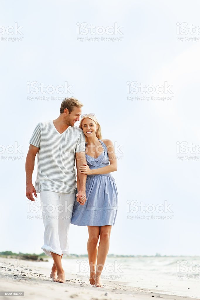 Romantic young couple walking on beach - copyspace royalty-free stock photo
