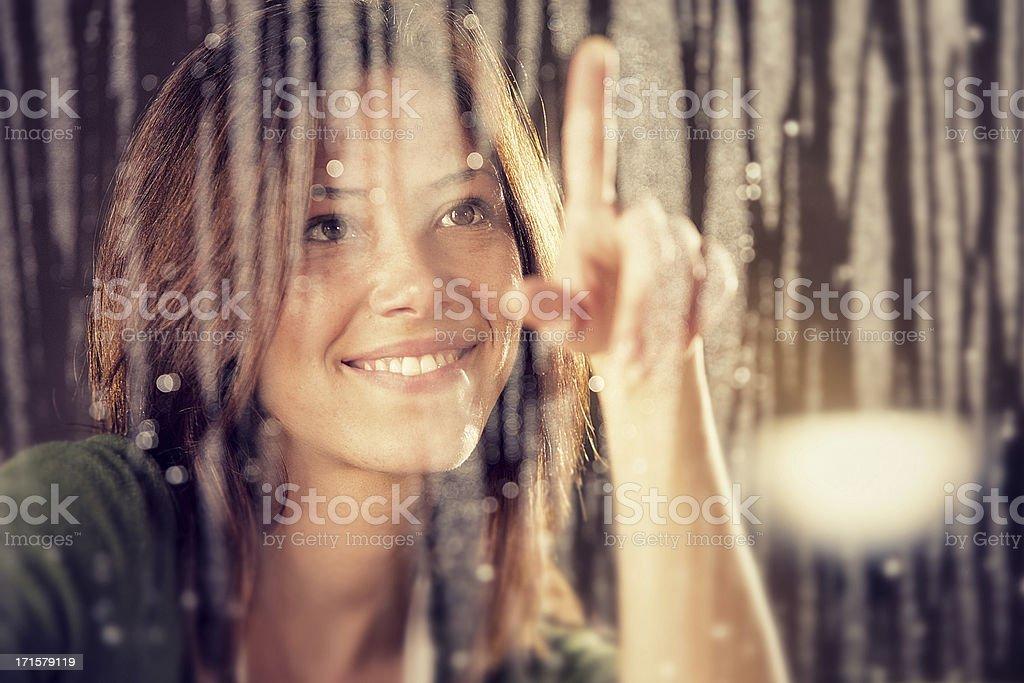 romantic young girl looks at  rain through the window stock photo