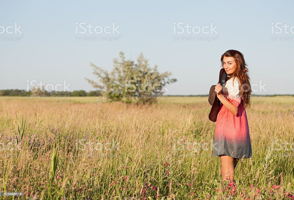 Romantic young woman in hat standing on meadow stock photo