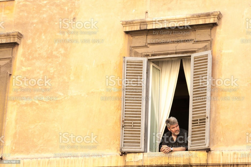 Rome, Italy: Man Leans Out Window; White Curtains, Yellow Building stock photo