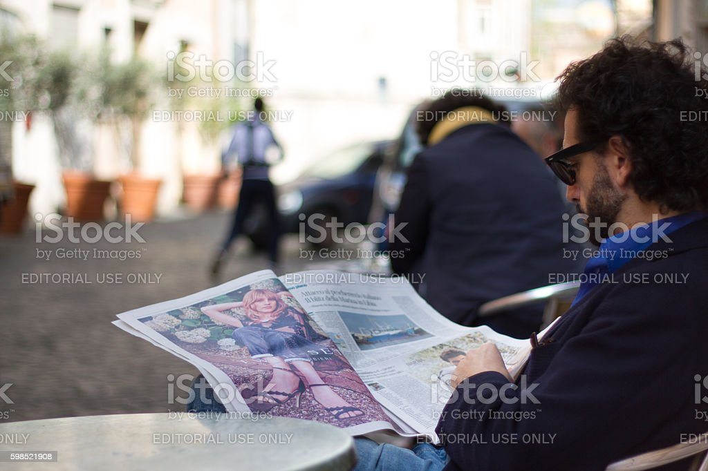 Rome, Italy: Man Reading Newspaper at Outdoor Cafe Table stock photo