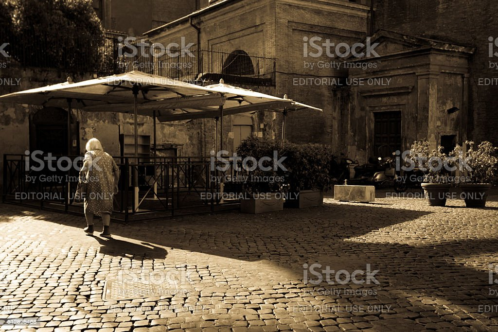 Rome, Italy: Senior Woman on Beautiful Empty Cobbled Piazza (Sepia) stock photo