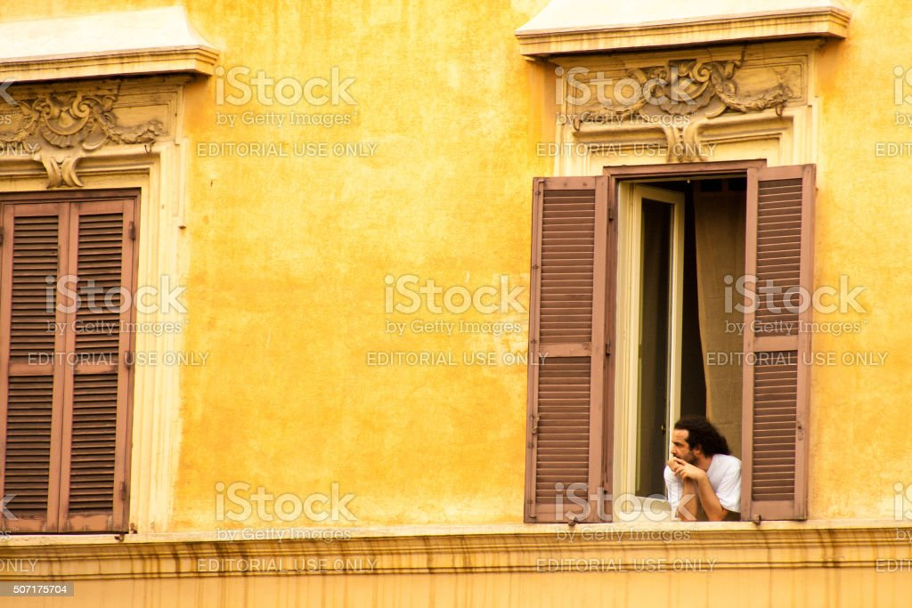 Rome, Italy: Young Man Leans Out Window, Yellow Building stock photo