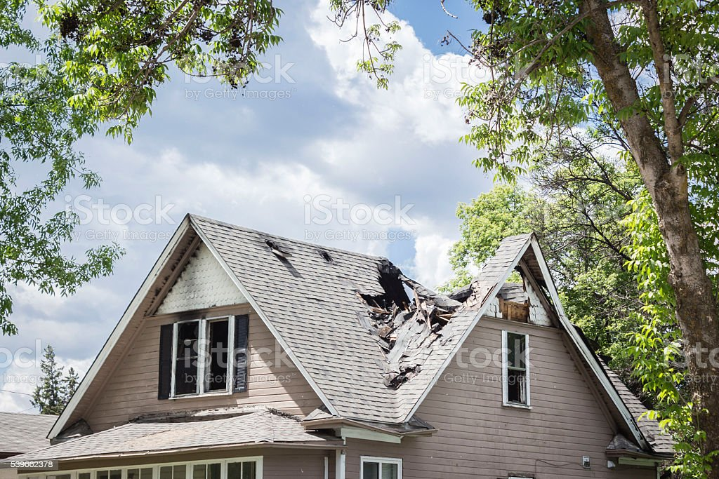 roof of a house burned and caved in. stock photo