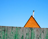 Roof of a house with a pipe behind fence