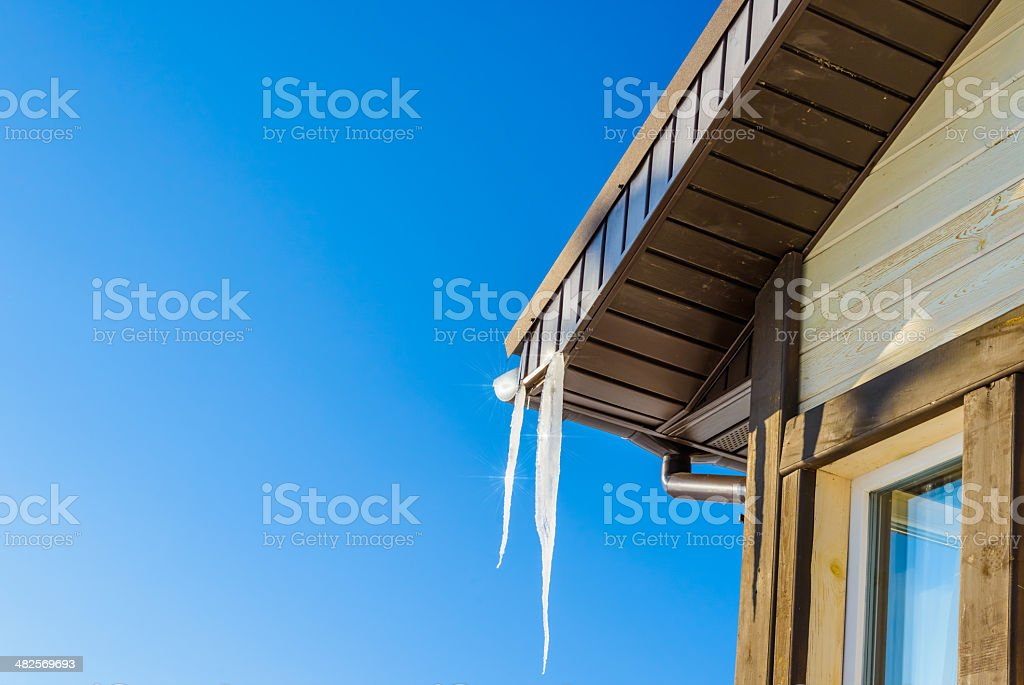 roof of  house with hanging icicles on blue sky background stock photo