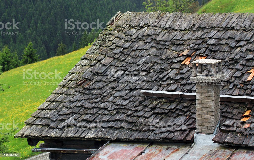roof of wooden shingles and stone chimney stock photo