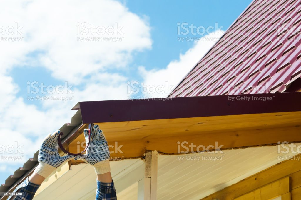 Roof repair by a master against a blue sky background stock photo