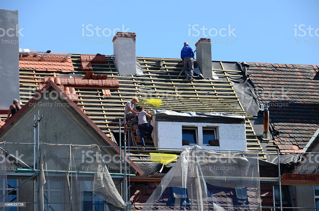 Roof repair - laying tiles stock photo