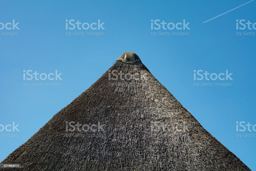roof tile op top of thatched roof stock photo