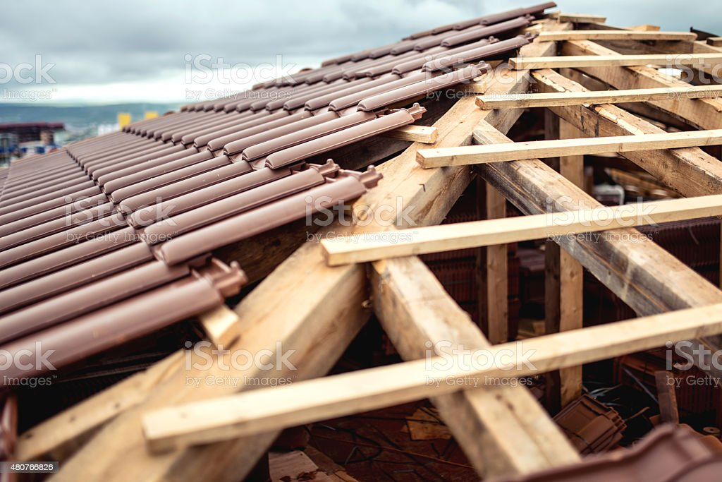 Roof under construction with stacks of brown tiles covering house stock photo