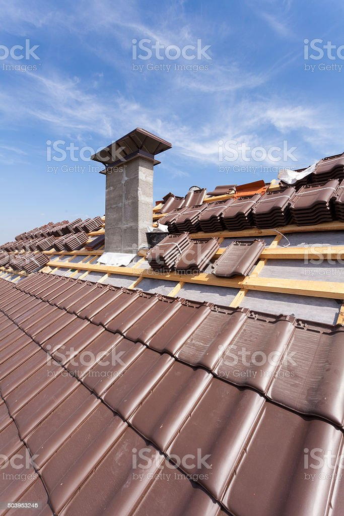 Roof under construction with stacks of roof tiles stock photo