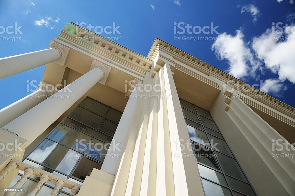 Roof, windows and columns of new building on blue sky stock photo