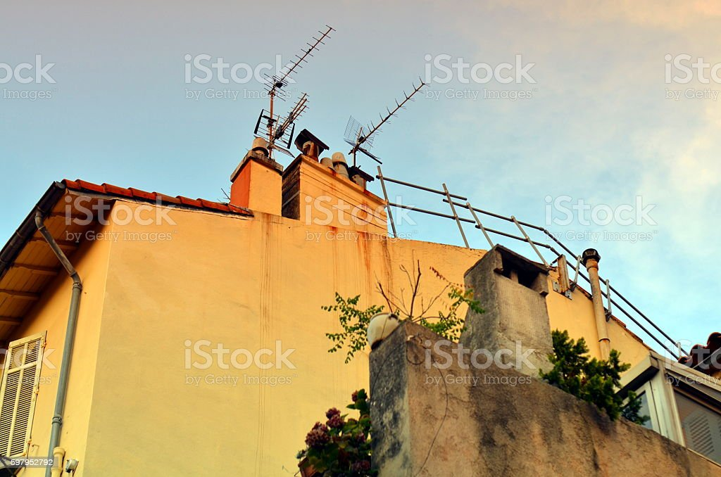 roof with antenna and cables of a french building stock photo