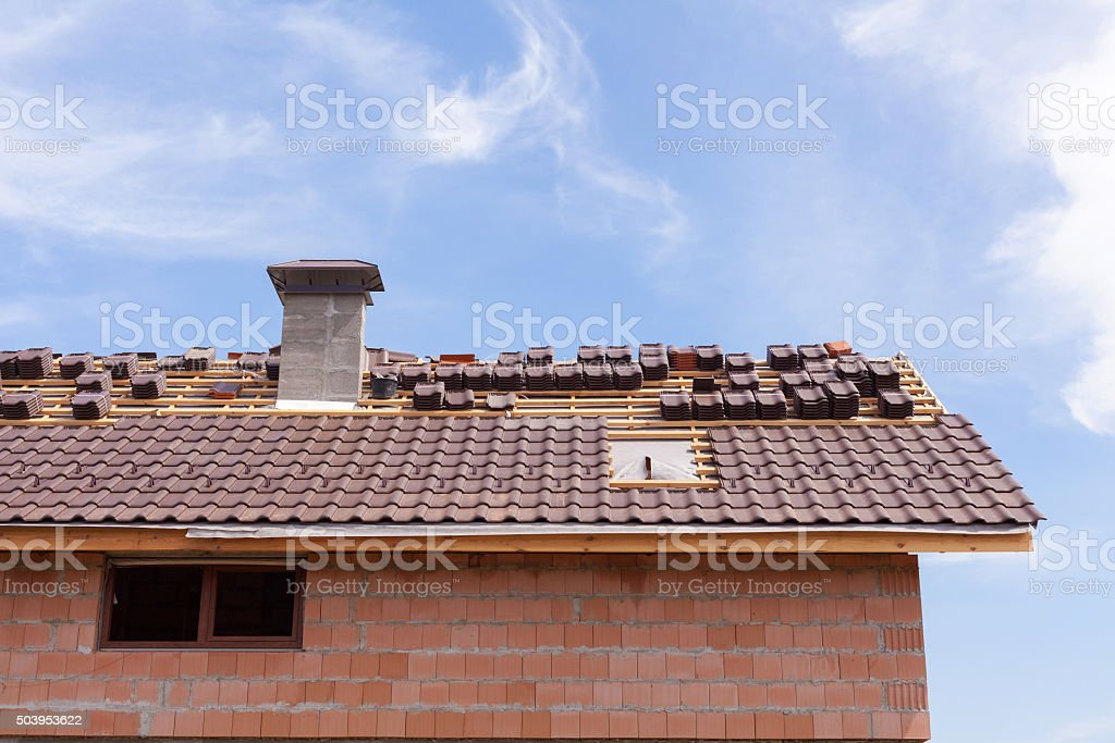Roof with chimney under construction with stacks of roof tiles stock photo
