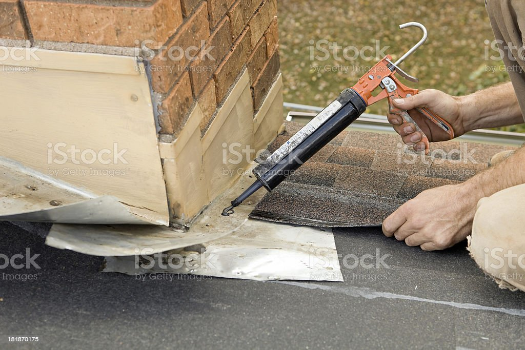 Roofer Applying Caulk to House Chimney Flashing stock photo