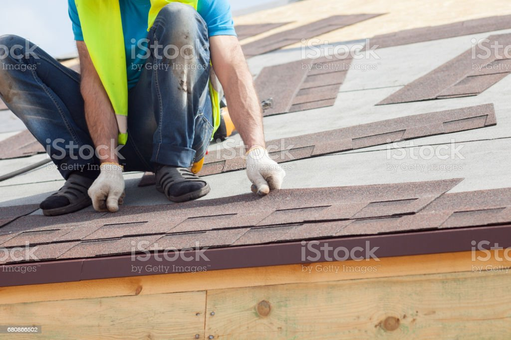 Roofer builder worker installing  Asphalt Shingles or Bitumen Tiles on a new house under construction stock photo
