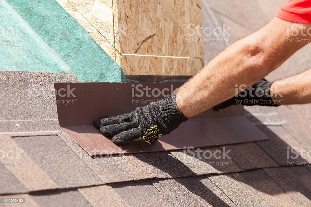 Roofer builder worker installing shingles on a new wooden roof stock photo