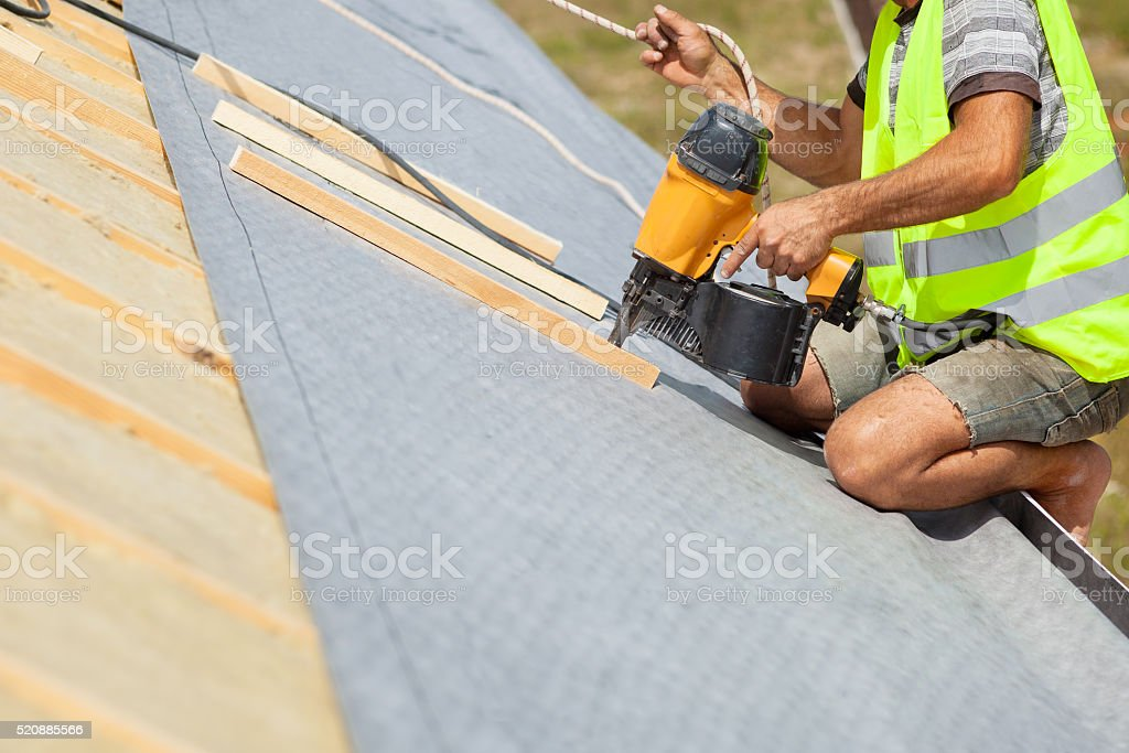 Roofer builder worker use automatic nailgun to attach roofing membrane stock photo