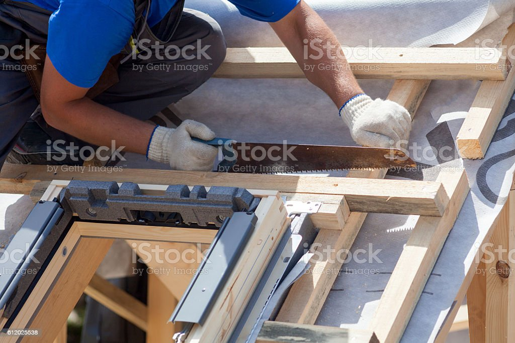 Roofer builder worker use saw to cut a wooden beam stock photo