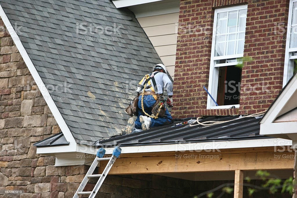 A roofer fixing the roof of a brick house stock photo
