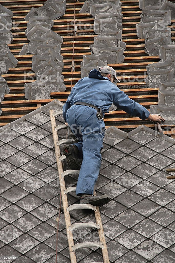 roofer in blue work clothes royalty-free stock photo