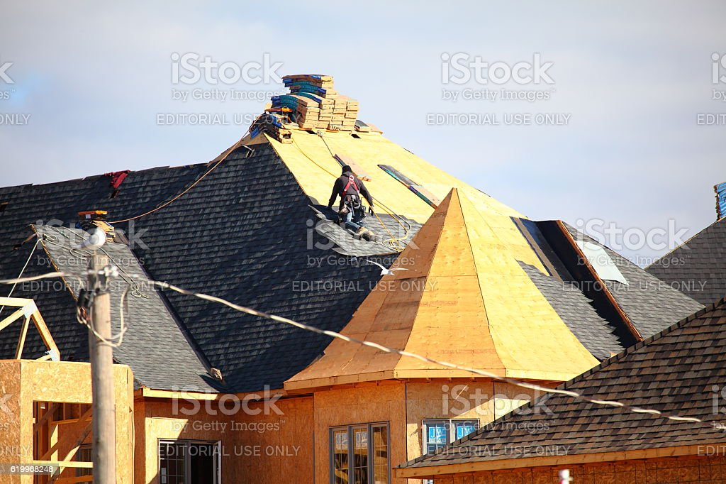 Roofer installing shingles on a new roof stock photo