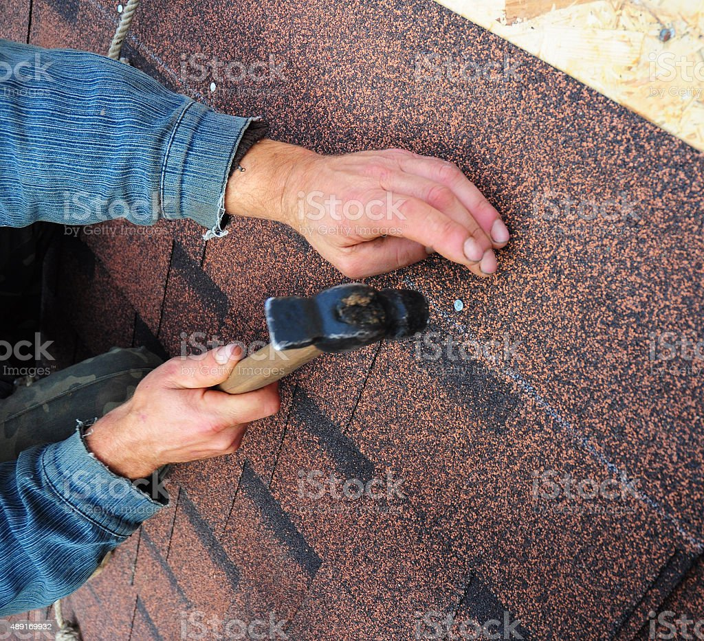 Roofer installs bitumen roof shingles stock photo