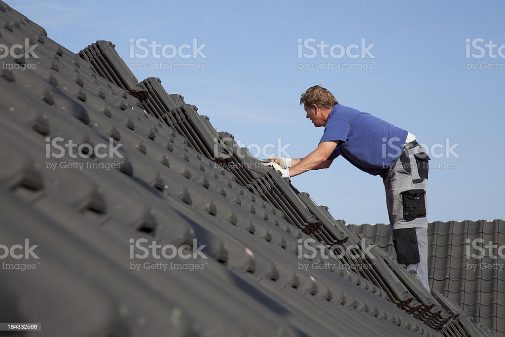 Roofer is working hard on a roof. royalty-free stock photo