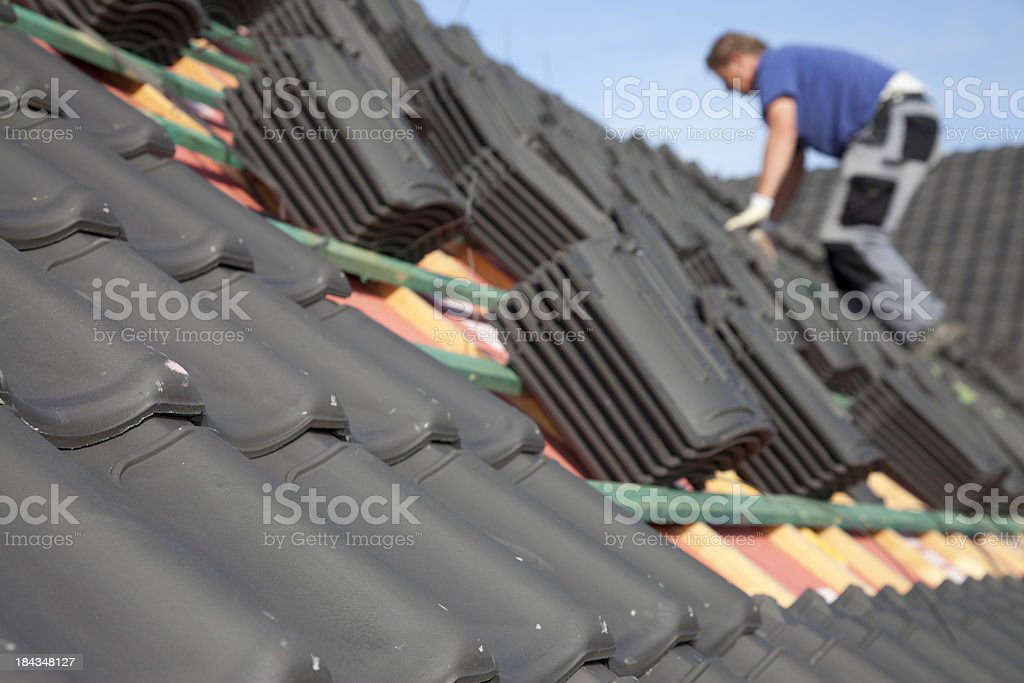 Roofer is working hard on a roof. stock photo