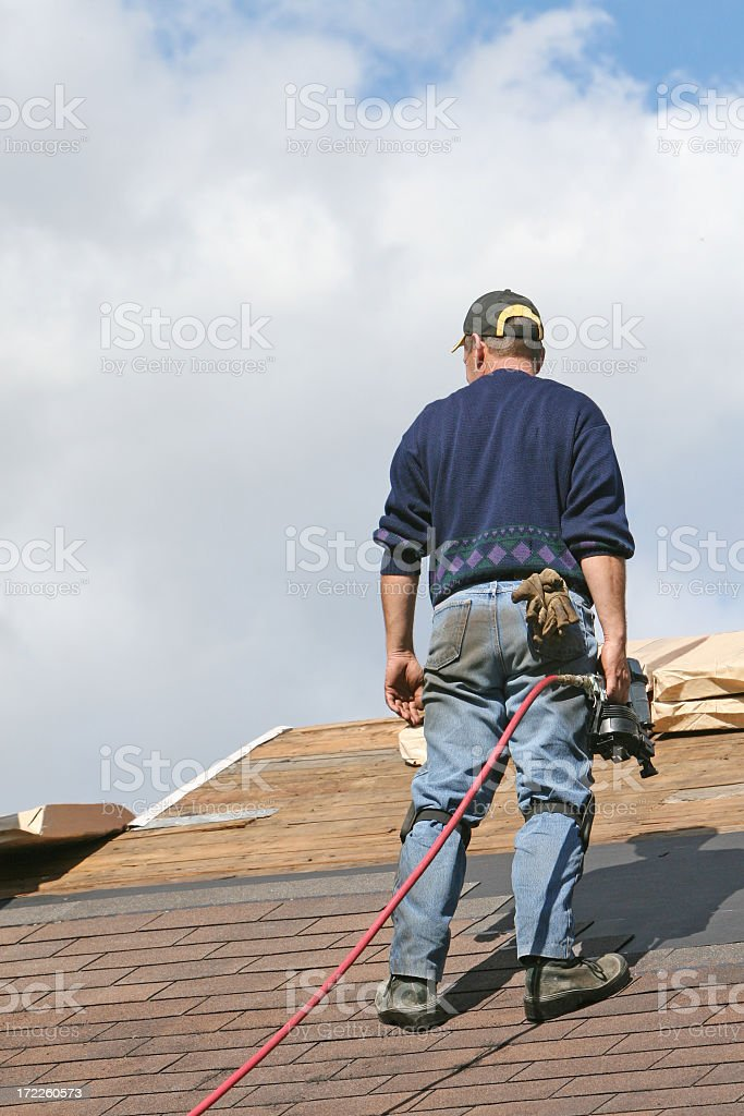 Roofer looking at shingles while holding a power tool royalty-free stock photo