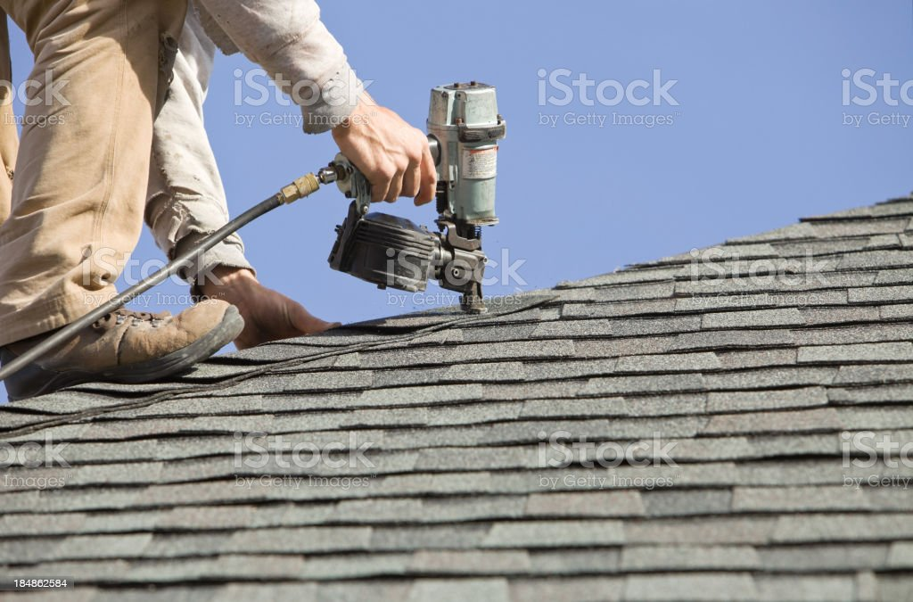 Roofer Nailing Cap Shingle to a New House Roof stock photo