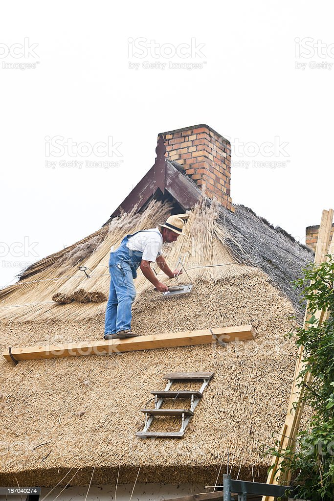 Roofer on a thatched roof royalty-free stock photo