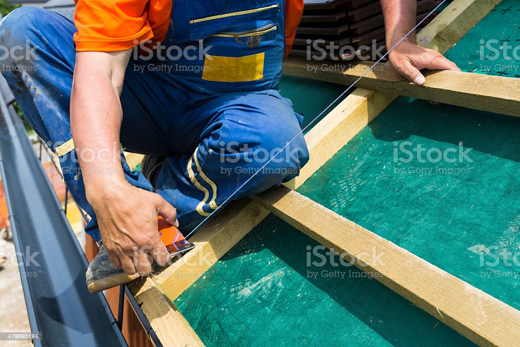 Roofer on the rooftop prepairing wooden construction. stock photo