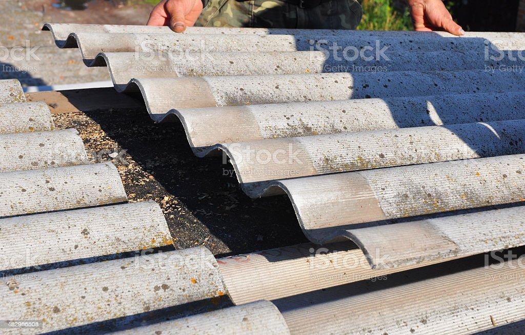 Roofer Repair Dangerous Asbestos Old Roof Tiles. Roofing Repair stock photo