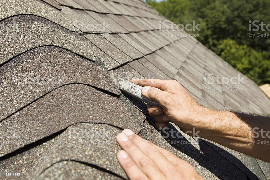 Roofer Trimming a New Shingle on Home Construction Project royalty-free stock photo